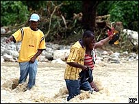 Jamaicans cross a flooded road