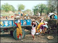 Indian villagers build a canal