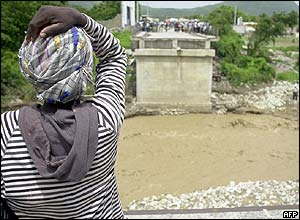 A woman in Grand Goave, Haiti, looks at what is left of the local bridge after floods caused by Hurricane Dennis swept it away.