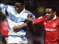 Dennis Bailey (l) takes on Man Utd's Paul Parker