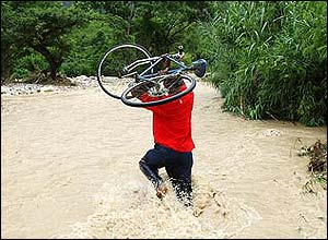 A boy carries his bicycle through flowing floodwaters after Hurricane Dennis struck Jamaica