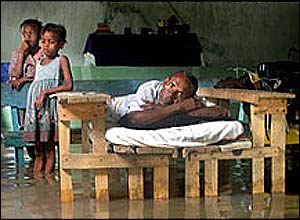 Two children and a man look on after being hit by flood waters