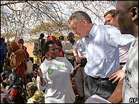Britain's International Development Secretary Hilary Benn, listens to an aid worker at a feeding centre in Wajir district, northern Kenya