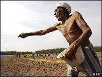 Indian farmer sprinkles fertilizer in his field near Cuddalore in Tamil Nadu