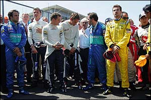 The drivers hold a minute's silence before the start of the race