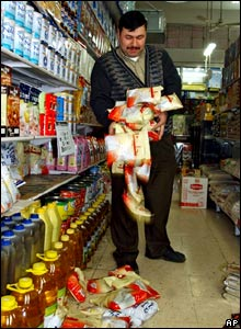 A shop owner in Hebron, in the West Bank, takes Danish milk powder off the shelves