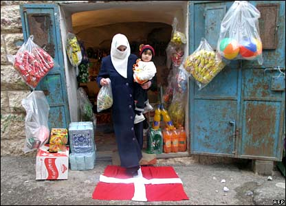 A woman in the West Bank town of Hebron walks over a Danish flag