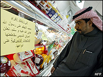 Saudi man looking at sign urging a boycott of Danish products
