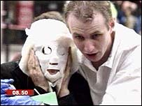 Paul Dadge helps a woman who's wearing a mask to protect her burns