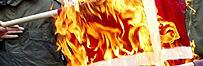Muslim youth members of the Al-Aqsa Martyr brigades burn the Danish flag in Kalandia