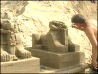 Artist works on sand sculpture