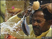 Coconut being smashed by an Indian man