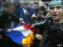 Muslim youth members of the Islamic movement Hamas burn the French flag