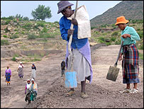 Women building a dam by hand