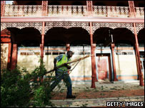 A worker removes a tree felled by Hurricane Dennis in Pensacola, Florida