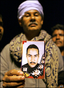 A man holds a photo of his cousin in Safaga