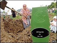 A child watches as a Bosnian Muslim woman digs a grave for a relative shortly before the burial