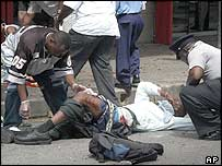 Police and pedestrians help one of the wounded in Port of Spain