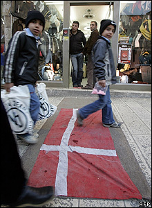 Palestinians walk on a Danish flag