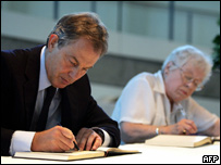 Tony Blair signs the book of condolences, next to a member of the public (Jean Vallaton)
