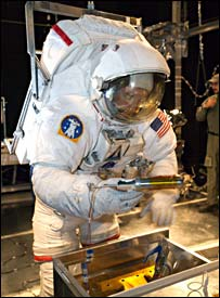 An EVA suited James Reilly tries out a panel repair kit (Nasa)