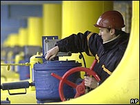 Worker turning a valve on a gas pipeline