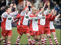 The Spartans players applaud their fans at full-time