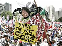 A picture of Philippine President Gloria Macapagal Arroyo is placed on a body of an insect effigy, in the financial district of Makati, south of Manila on Wednesday July 13, 2005.