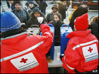American Red Cross workers hand out hot drinks to commuters, AP