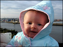 A smiling baby overlooking Aberdeen harbour