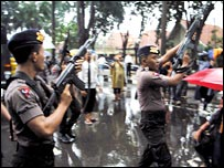 Indonesian police officers fire warning shots at a demonstration outside the US consulate in Surabaya