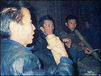 Hmong smoking opium in traditional fashion