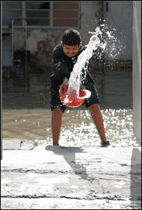 Young Iraq boy throws water out of bucket in Baghdad, Iraq