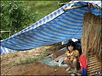 A young ethnic Hmong refugee from Laos shelters under a plastic tent along a roadside in Phetchabun province in north-eastern Thailand, Sunday, July 10, 2005.