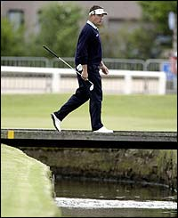 England's Lee Westwood shows his dejection as he walks to the first green after finding water with his second shot