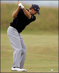 Retief Goosen of South Africa hits his approach shot on the fourth hole