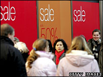 Shoppers walking past sale signs