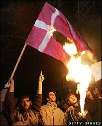 Protestors burn a Danish flag at the Danish embassy in Tehran