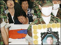 South Korean relatives of one of the soldiers killed in a shooting rampage cry beside the coffin during a joint funeral service at a military hospital in Sungnam, 25 June 2005