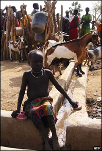 A young girl sits in front of a watering hole in Sudan's southern region (file image)