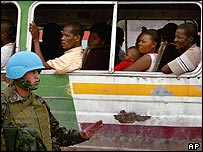 UN peacekeeper standing next to a bus full of Haitian civilians
