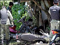 Thai border police officers examine the scene where a bomb exploded in Yala province, southern Thailand Friday, July 15, 2005