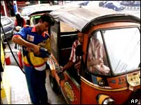 Bajaj drivers fill up at a petrol station in Jakarta, Indonesia
