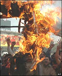 Pakistani journalists burn an effigy in  protest against cartoons of the Prophet Muhammad
