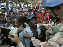 Voters force they way past UN soldiers at a polling station in Haiti