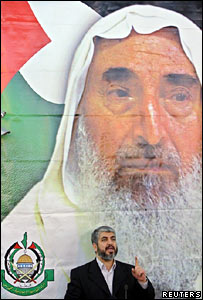 Khaled Meshaal speaks in front of a poster of Sheikh Ahmed Yassin