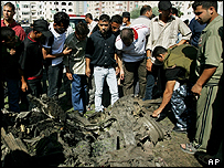 Palestinians gather around a destroyed van in Gaza city