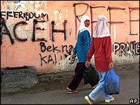 Women walking past graffiti on a street in Aceh
