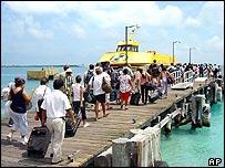 Holidaymakers board an island ferry