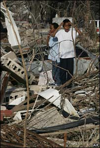 Children survey the damage done to their New Orleans home by Hurricane Katrina